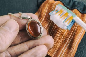 Cleaning silver jewellery with and toothbrush and baking soda